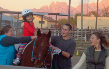 Image of assisting a rider at the NMSU Therapeutic Riding program